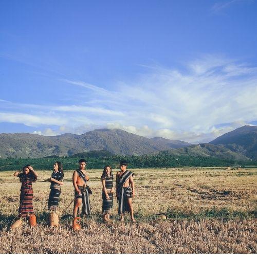 Personas en un campo y unas montañas