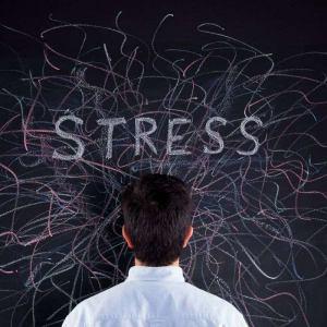 Hombre mirando una pizarra con la palabra estrés